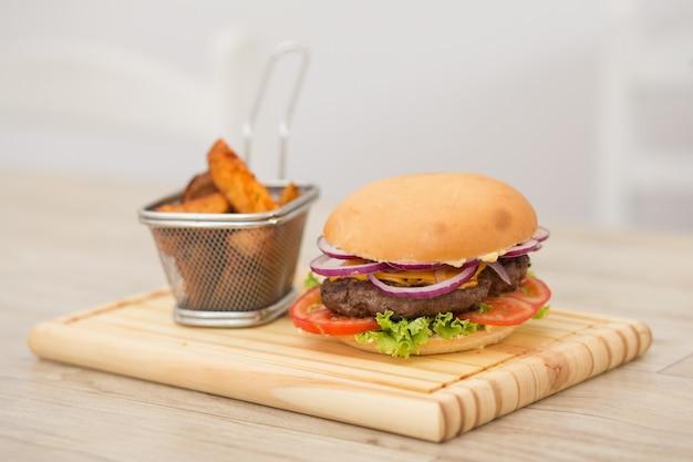 Verse zelfgemaakte hamburger op kleine snijplank met gegrilde aardappelen, geserveerd met ketchupsaus en zeezout over houten tafel met grijze houten achtergrond.