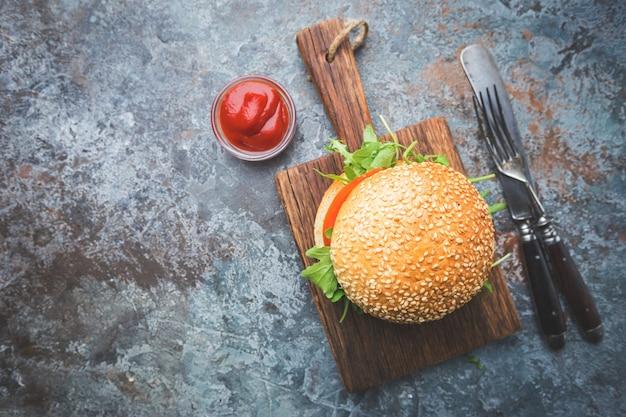 Verse zelfgemaakte hamburger op serveerplank met pikante saus en kruiden over donkere stenen achtergrond. bovenaanzicht met kopieerruimte
