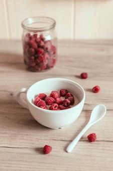 Verse zelfgemaakte havermout met frambozen in een kom op de tafel in de keuken.