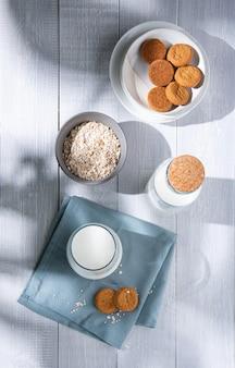 Verse zelfgemaakte havermoutkoekjes met een glas veganistische melk op een witte houten tafel. ochtendlicht en bovenaanzicht