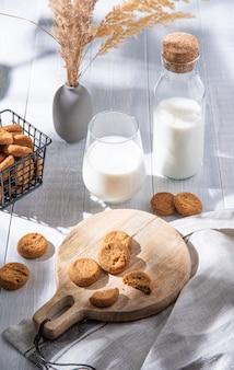 Verse zelfgemaakte havermoutkoekjes op houten snijplank met een glas veganistische melk op een witte houten tafel