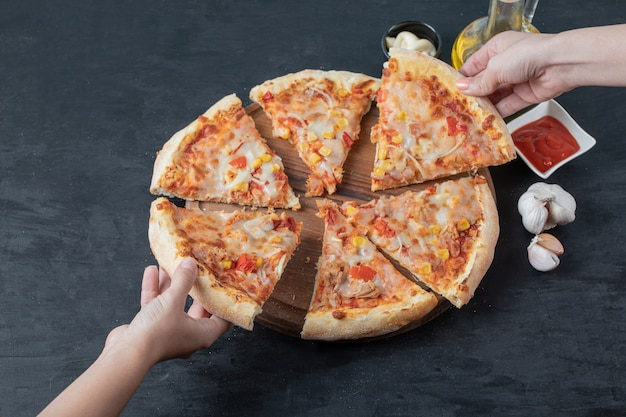 Verse zelfgemaakte heerlijke pizza. vrouwelijke hand die pizzapunt over zwarte tafel neemt.