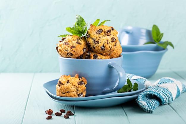 Verse zelfgemaakte heerlijke rozijnenmuffins in blauwe kop, suikervrij. gezond voedselconcept met exemplaarruimte