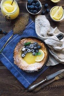Verse zelfgemaakte hollandse baby pannenkoek met lemon curd en bosbessen in ijzeren koekenpan