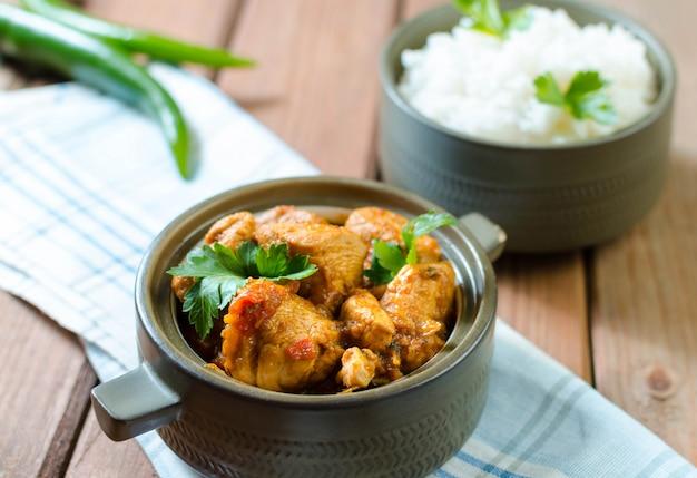 Verse zelfgemaakte kip curry met kille in vintage keramische kom.