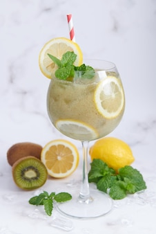 Verse zelfgemaakte kiwi-smoothies met citroen, melk, munt en honing. gezonde biologische drank. close-up en selectieve aandacht. vers gemengd groen fruit, welzijn en gewichtsverlies concept.