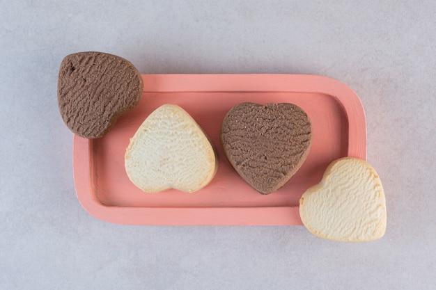 Verse zelfgemaakte koekjes in hartvorm op roze plaat