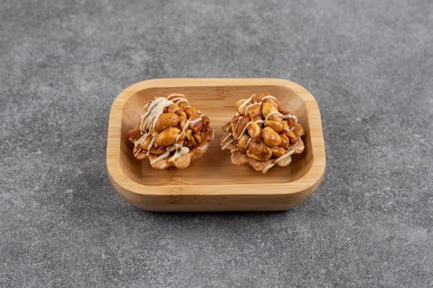 Verse zelfgemaakte koekjes in houten kom over grijze tafel.