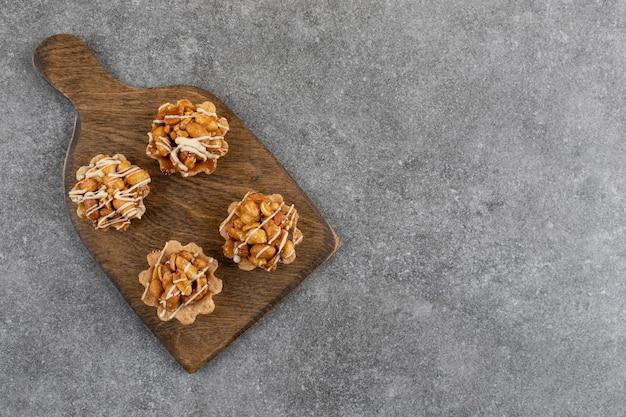 Verse zelfgemaakte koekjes op een houten bord over grijze ondergrond.