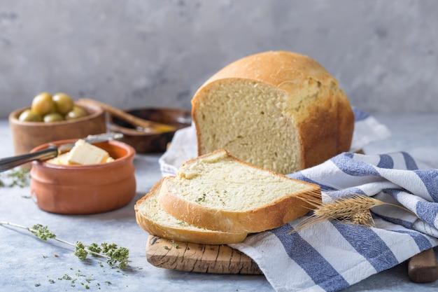 Verse zelfgemaakte krokante brood en plakjes met olijfolie, boter en groene olijven, bovenaanzicht. bakken