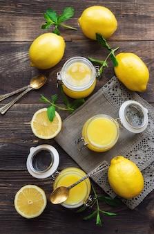 Verse zelfgemaakte lemon curd in glazen potten op rustieke houten achtergrond. bovenaanzicht.