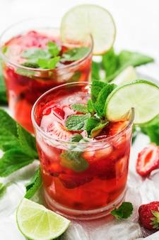 Verse zelfgemaakte limonade met aardbeien, limoenen en muntblaadjes