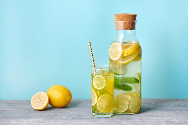 Verse zelfgemaakte limonade met limoen en munt in het glas met papieren stro en fles op helderblauwe achtergrond