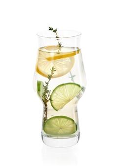 Verse zelfgemaakte limonade met limoen en tijm in ijsglas op witte achtergrond