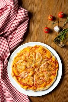 Verse zelfgemaakte margarita pizza op een houten achtergrond in samenstelling met een rode doek en olijfolie. italiaanse keuken. bovenaanzicht eten foto