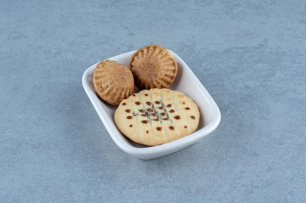 Verse zelfgemaakte muffins en cookie in witte keramische kom.