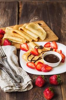 Verse zelfgemaakte pannenkoeken met aardbeien en chocoladesaus op rustieke houten achtergrond.