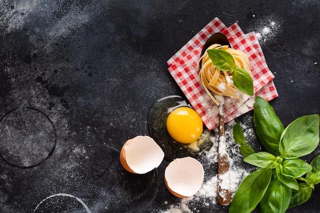 Verse zelfgemaakte pasta tagliatelle op houten lepel met de tomaten van deegwareningrediënten, rauw ei, basilicumblad op de donkere concrete lijstlijst. koken concept. bovenaanzicht met kopie ruimte.