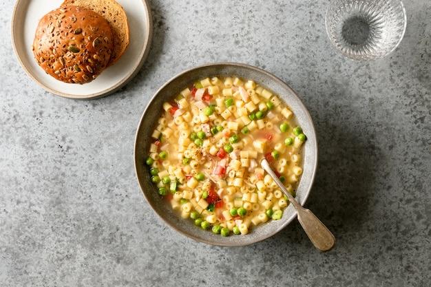 Verse zelfgemaakte soep van erwten, groenten, tomaten, ham, ditalini soep pasta-ei op grijze tafel.