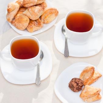 Verse zelfgemaakte suikerkoekjes met thee op witte lijst met zonlicht. goedemorgen of dag concept.