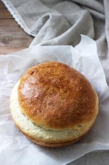 Verse zelfgemaakte tarwe gist brood op een linnen tafellaken. rustieke stijl.
