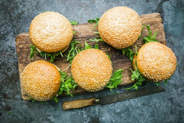 Verse zelfgemaakte veganistische hamburger op serveerplank over donkere stenen achtergrond. bovenaanzicht met kopieerruimte