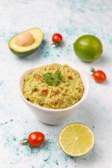 Verse zelfgemaakte warme guacamole saus met ingrediënten, bovenaanzicht