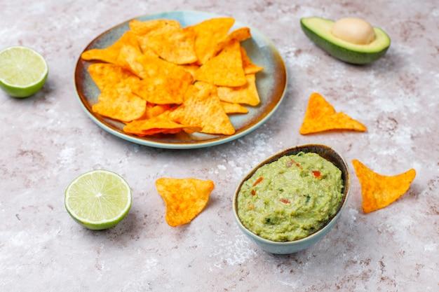 Verse zelfgemaakte warme guacamole saus met nacho's, bovenaanzicht