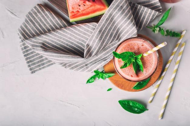 Verse zelfgemaakte watermeloen en basilicum smoothie in glas op witte betonnen ondergrond