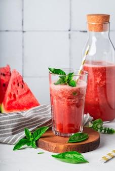 Verse zelfgemaakte watermeloen en basilicum smoothie in glas op witte tegel achtergrond