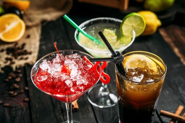 Verse zoete alcoholcocktails in verschillende glazen, lang kosmopolitisch eiland en margarita op de donkere houten achtergrond, horizontale close-up ,.