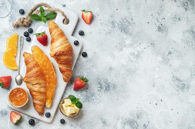 Verse zoete croissants met boter en sinaasappeljam voor het ontbijt. continentaal ontbijt op een witte betonnen tafel. bovenaanzicht met kopie ruimte. plat leggen.
