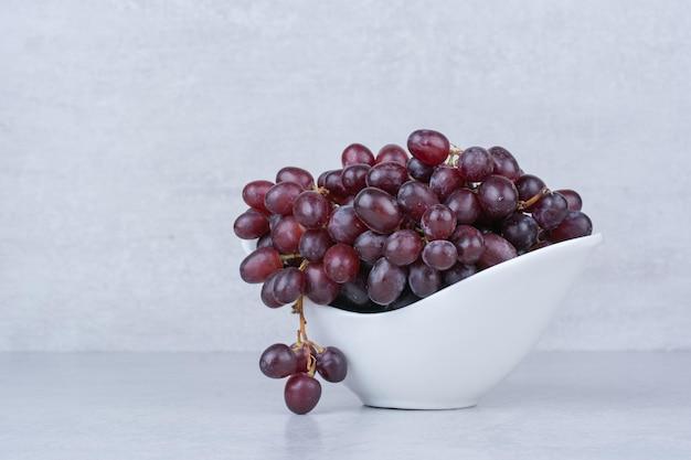 Verse zoete druiven in witte plaat op witte achtergrond. hoge kwaliteit foto