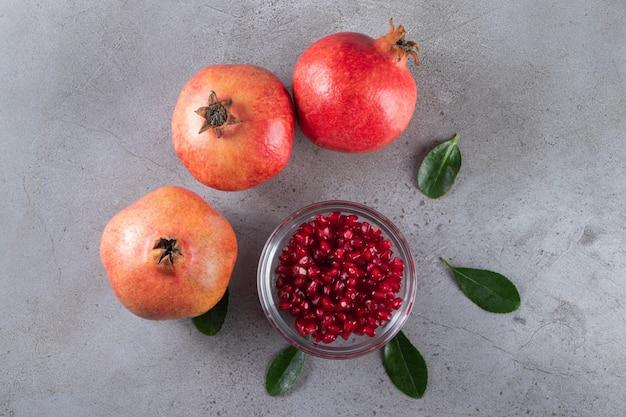 Verse zoete granaatappels met bladeren op stenen tafel.