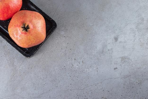 Verse zoete granaatappels op stenen tafel.