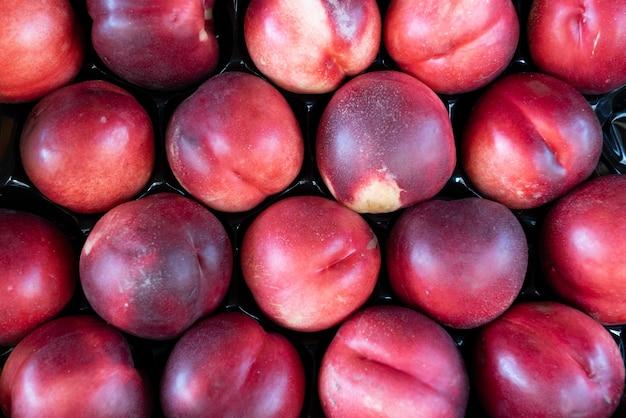 Verse zoete rijpe perziken op marktkraam