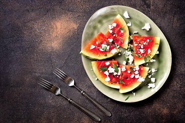 Verse zomer gegrilde watermeloen salade met fetakaas, mint, uien op bruine achtergrond