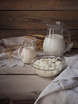 Verse zuivelproducten: melk, kwark, zure room en tarwe op rustieke houten achtergrond. biologische landbouw zuivel concept.
