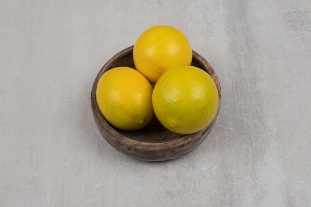 Verse zure citroenen in houten kom.