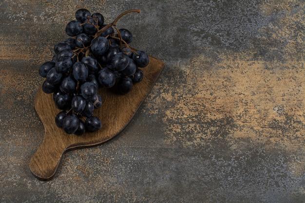 Verse zwarte druiven op een houten bord.
