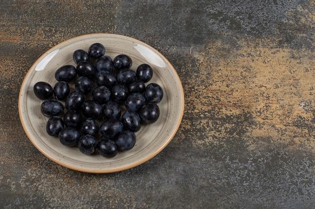 Verse zwarte druiven op keramische plaat.