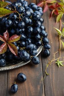 Verse zwarte druiven op verzilverd tafelgerei