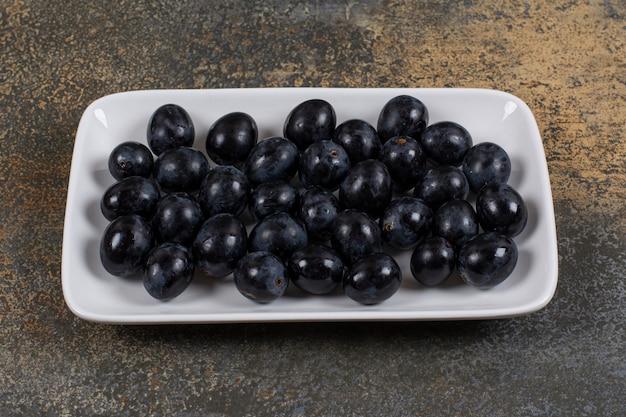 Verse zwarte druiven op witte vierkante plaat.