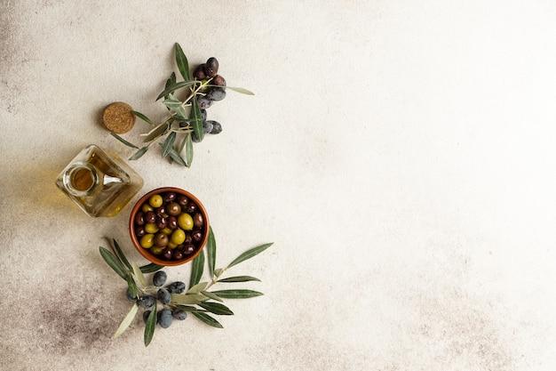 Verse zwarte en groene olijven en olijfolie op betonnen tafel. bovenaanzicht