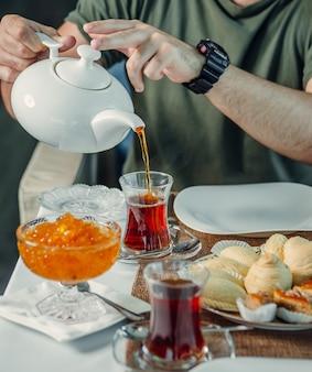 Verse zwarte thee met jam op tafel