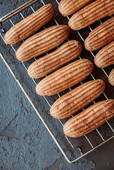Versgebakken aromatische custardcakes koel op het rooster op een donkere gestructureerde achtergrond
