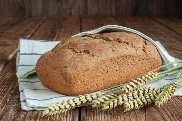 Versgebakken brood met een theedoek en oren op een rustieke houten achtergrond