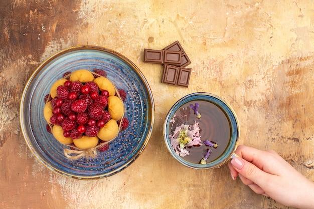 Versgebakken cadeau cake chocoladereep en een kopje thee op gemengde kleur tabel stock beeld