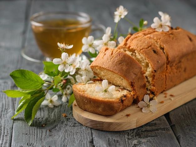 Versgebakken cake met rozijnen in kersenbloemen en thee op een houten tafel. heerlijke zelfgemaakte taarten.