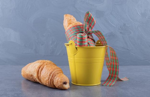 Versgebakken croissant in gele emmer over grijze achtergrond.